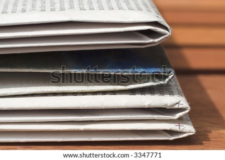 Macro of folded newspapers on a wooden table.