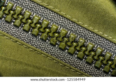 macro of green plastic nylon zipper - stock photo