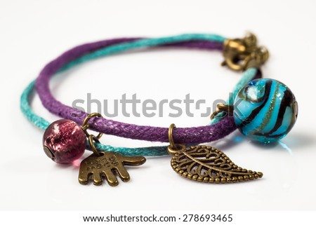 Macro of handmade bracelet made with leather straps and antique gold isolated on white background - stock photo