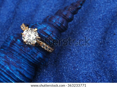 macro of jewelry ring with big diamond on blue seashell and sand background
