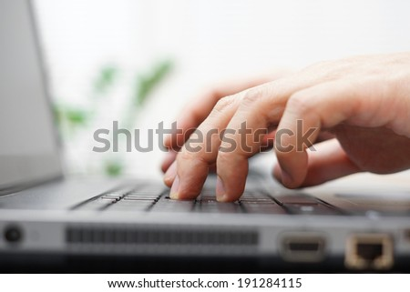macro of male hands typing on a laptop - stock photo