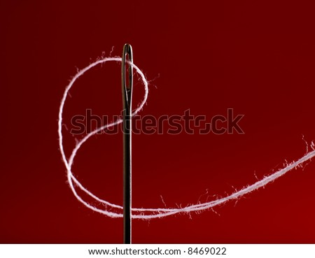 Macro of needle with white thread against red background. Shallow DOF. - stock photo