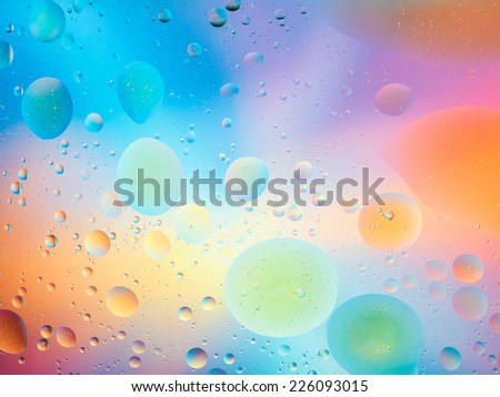 macro of oil mixed with water on colorful background - stock photo