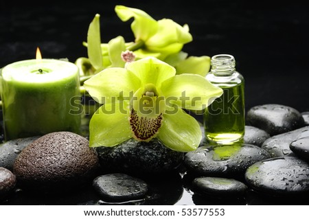 Macro of orchid and massage oil and candle with water drops - stock photo