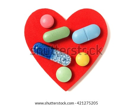 Macro of pills and capsules on red heart - stock photo