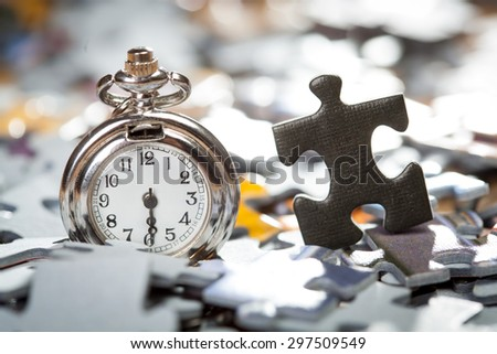 Macro of pocket watch and black jigsaw piece on a blurred pile of jigsaw puzzle pieces. Shallow depth of field - stock photo