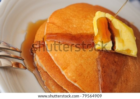 Macro of pouring delicious maple syrup on stack of pancakes. - stock photo
