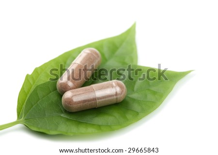 macro of prescription pills over green leaf isolated - stock photo