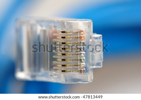 Macro of RJ45 network plug, showing the golden contacts, with blue network cable in background. - stock photo