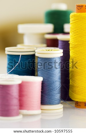 macro of thread in different colors. Focus on the yellow thread. - stock photo