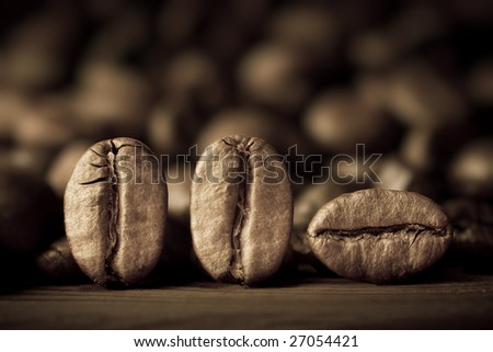 Macro of three coffee beans against blurry background. Shallow DOF. - stock photo
