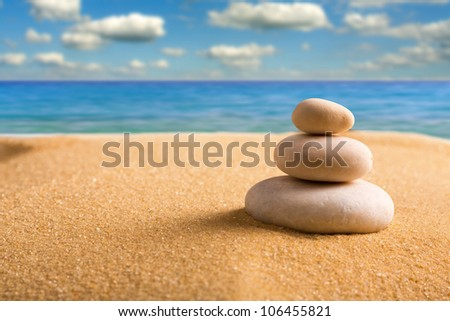 Macro of three staked zen stones on the beach - stock photo