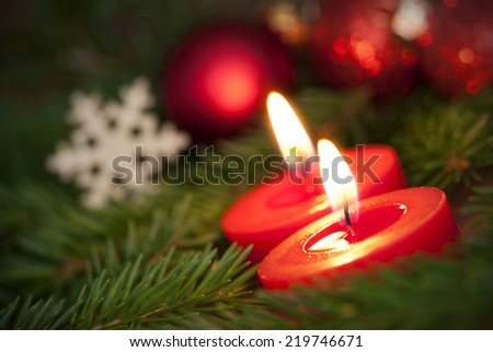Macro of two red Burning Candles giving a warm Light to the Christmas Decoration in the Background - stock photo