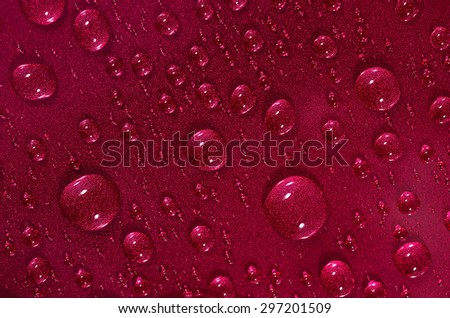 Macro of water drops on the red surface  - stock photo