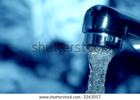 Macro of water flowing from a tap - shallow DOF - stock photo