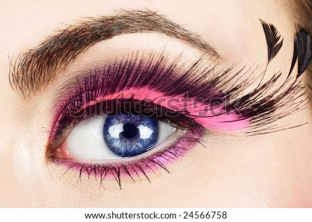 Macro of woman?s eye with long pink feather fake eyelashes - stock photo