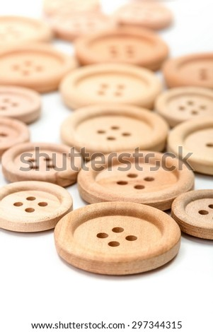 Macro of wooden buttons on white surface - stock photo