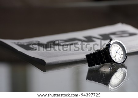 macro of wristwatch in front of newspaper, selective focus