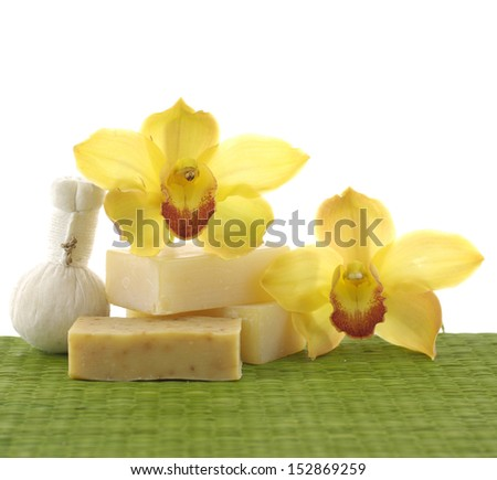 Macro of yellow orchid with natural handmade soap and massage ball on green mat - stock photo
