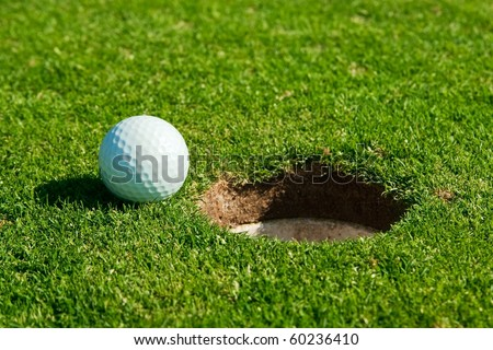 macro photo from golf ball and hole - stock photo