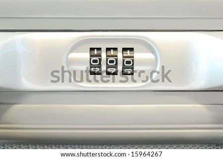 Macro photo of a combination lock on a silver color suitcase - stock photo