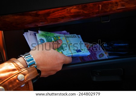 macro photo of a man's hand taking on glove compartment of cars a lot of money EUR. Inside car photo - stock photo
