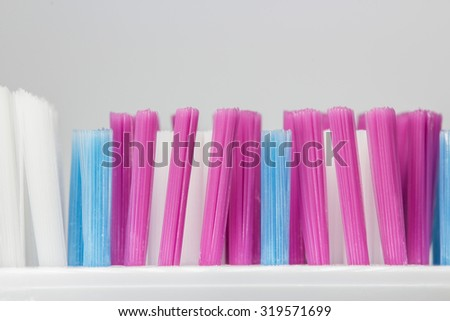 Macro photo of a toothbrush and bristles colored pink, blue and white and isolated on a white background. - stock photo