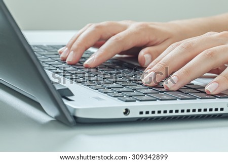Macro photo of female hands typing on laptop. businesswoman working at office computer.