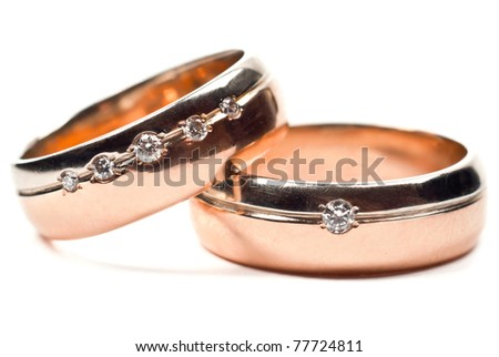 Macro photo of gold wedding rings with diamonds. White background.