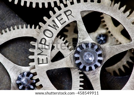 Macro photo of tooth wheel mechanism with EMPOWER concept words - stock photo