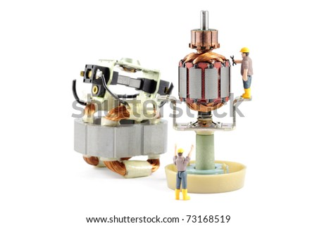 Macro photograph of a disassembled electric motor being worked on by two tiny toy engineers, concept. - stock photo