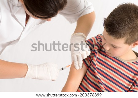 macro photograph of a doctor vaccinating a child - stock photo