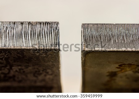 Macro photograph of Laser cut edge difference between half inch thick hot rolled steel and Pickled and oiled - stock photo