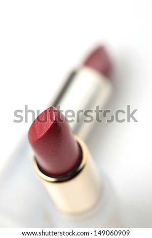 Macro photograph of two red lipsticks on plain background. - stock photo