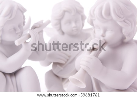 Macro photography of isolated porcelain figurines of angels playing musical instruments. - stock photo