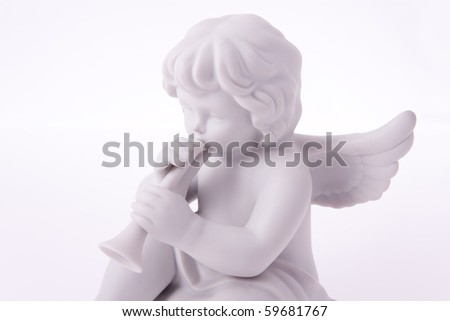 Macro photography of porcelain figurine of angel playing trumpet. - stock photo