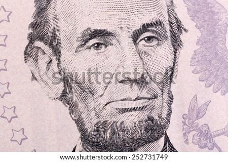 Macro portrait of Abraham Lincoln on five U.S. dollar bill. - stock photo