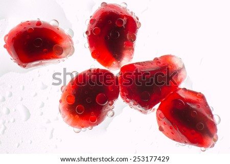 Macro ripe pomegranate fruit with water droplets - stock photo