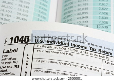 Macro, selective focus view of United States 1040 tax form booklet with tax table background.