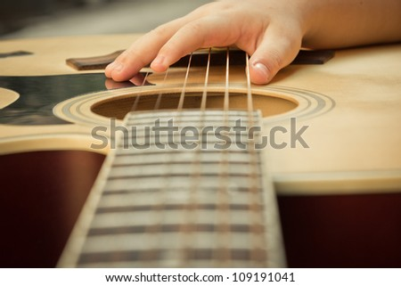 Macro shot down the fretboard of acoustic guitar with shallow depth of field - stock photo