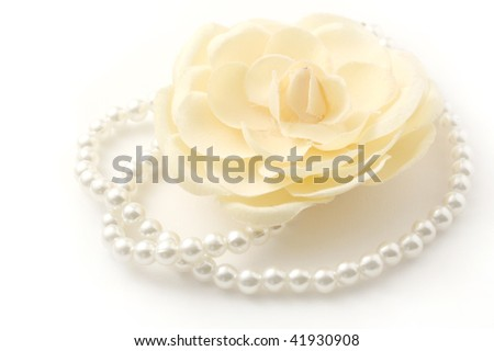 Macro shot of a beautiful flower and pearl necklace isolated on white. - stock photo