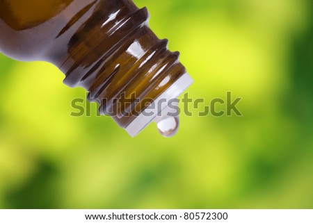Macro shot of a bottle with drop, with fresh foliage in the background. Focus on bottle - stock photo