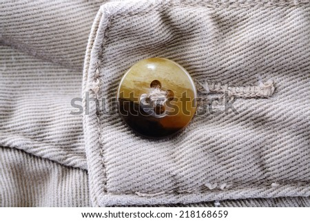 Macro shot of a button on a pair of man khaki trousers - stock photo