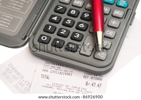 Macro shot of a calculator and a red pen over some receipts on white