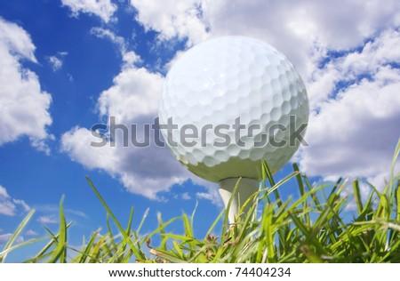 Macro shot of a golf ball against a beautiful blue sky - stock photo