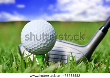 Macro shot of a golf club and ball with a beautiful blue sky in the background - stock photo