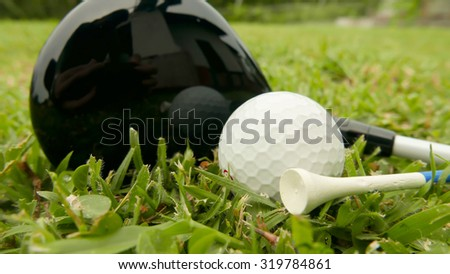 Macro shot of a golf club with ball and tee on the fairway grass - stock photo