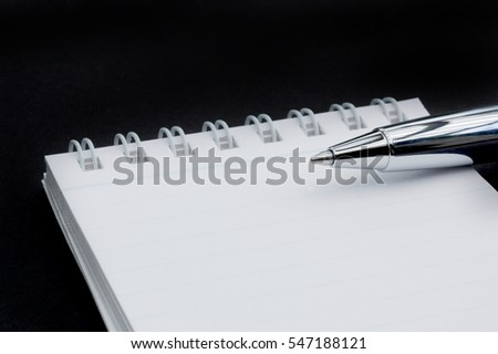 Macro shot of a silver pen on a small notepad on black