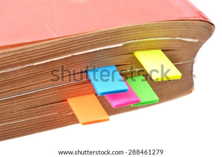 Macro shot of an old book with colorful tags between its pages - stock photo