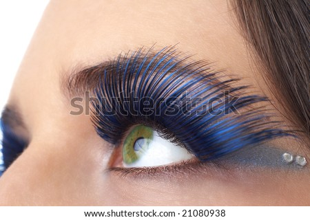 Macro shot of beautiful green eyes with bright blue make-up and fake eyelashes. Not a crop. Shallow depth of field - stock photo